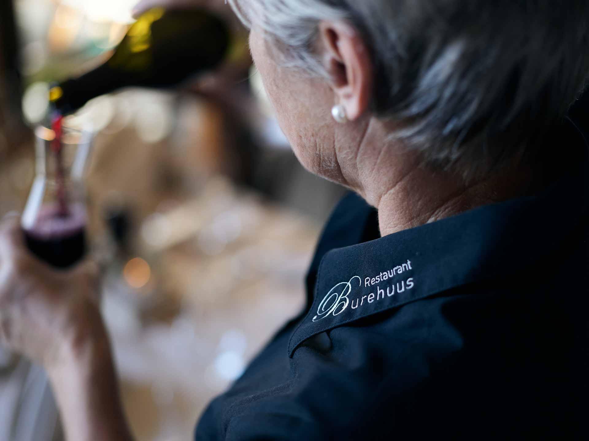 Frau schenkt Glas Wein ein