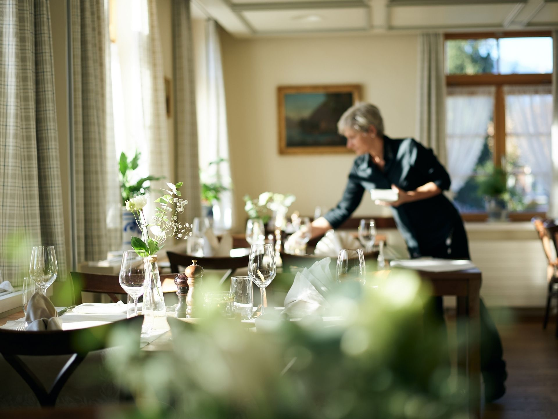 Frau dekoriert Tisch in Restaurant