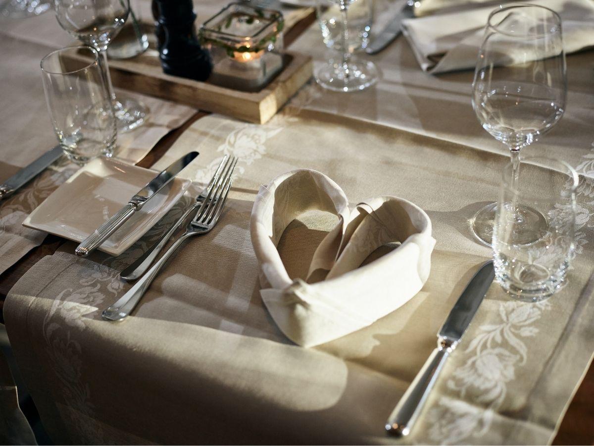 Gefaltete Serviette als Herz auf gedecktem Tisch