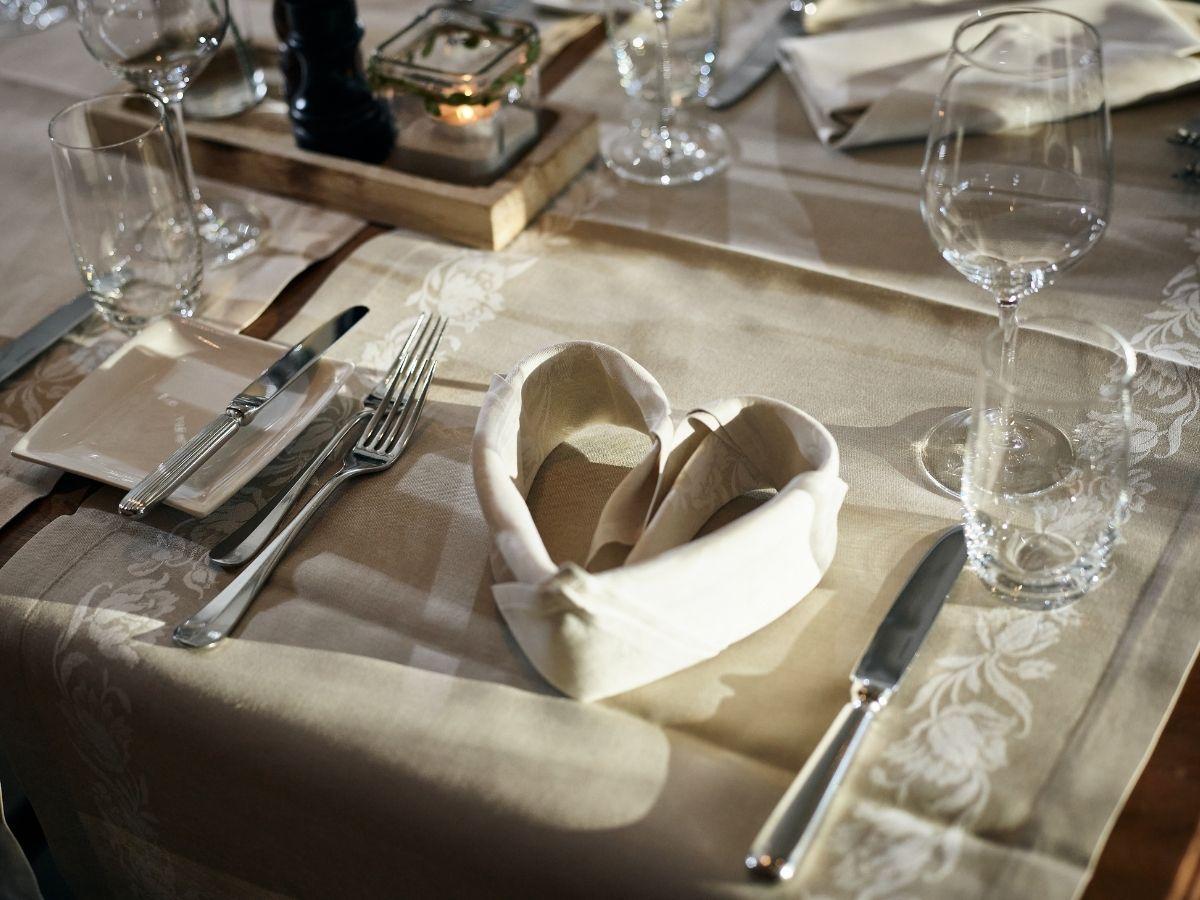 Gefaltete Herzserviette auf gedecktem Tisch