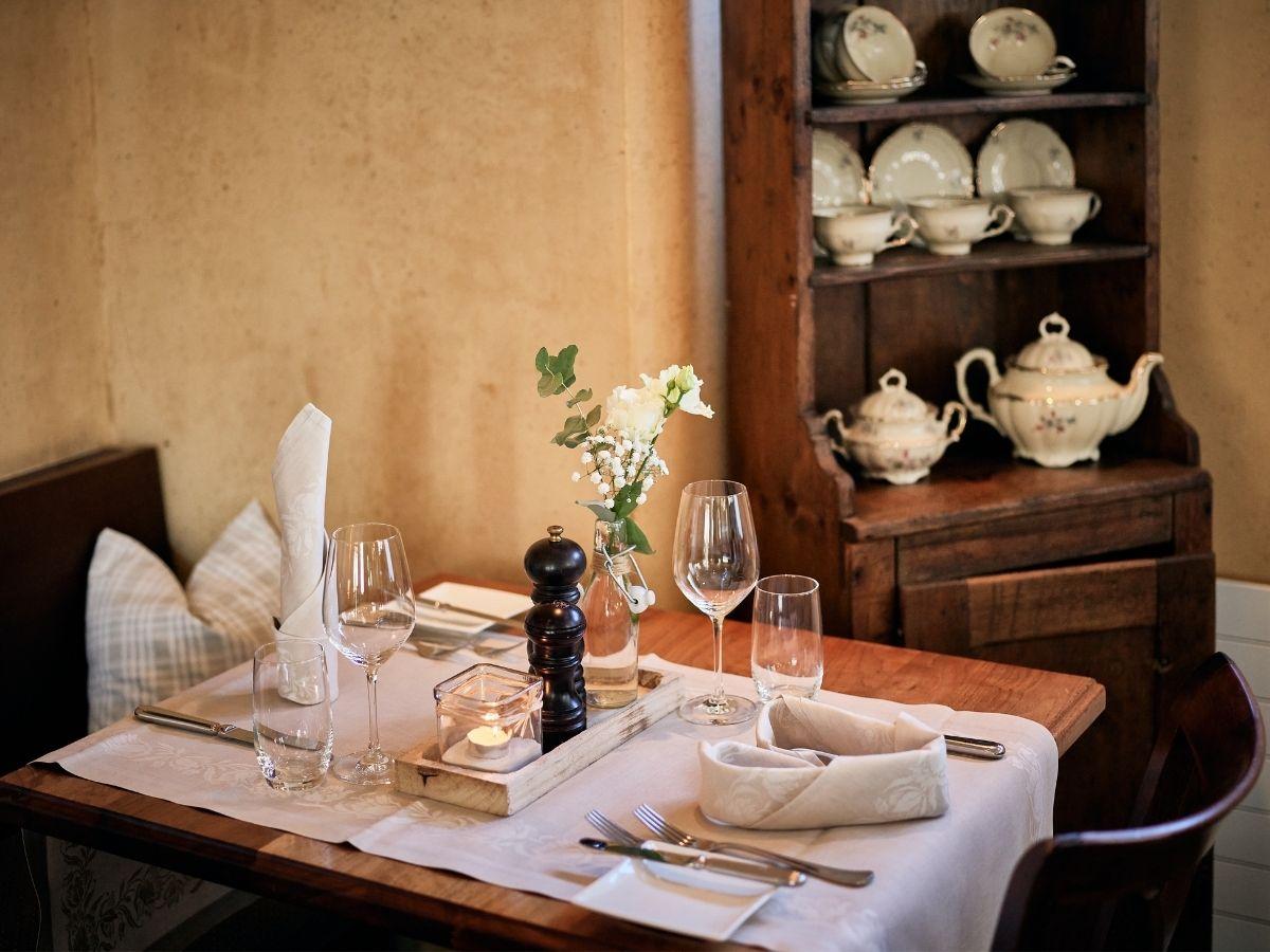 Gedeckter Tisch mit Dekoration und oranger Tapete im Hintergrund