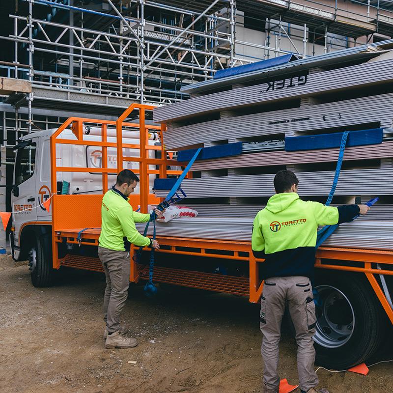 Toretto staff untying plasterboard from truck
