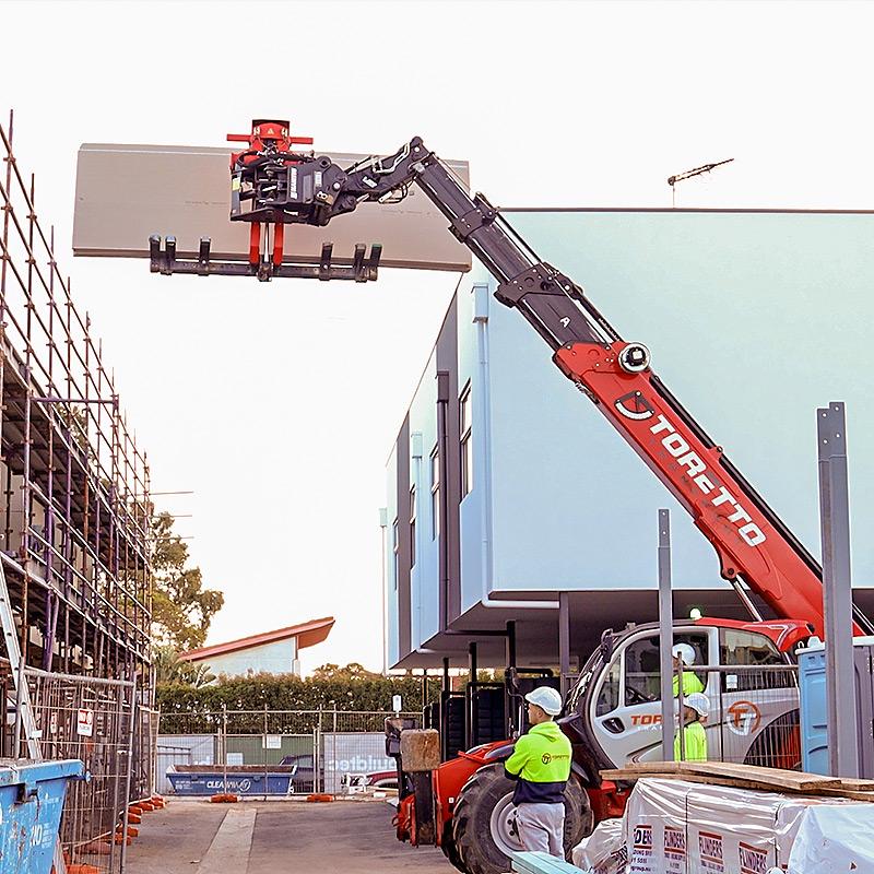 Telehandler lifting plasterboard up to third floor
