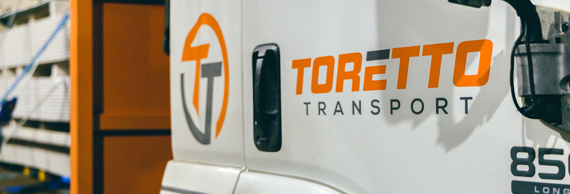 Close up of Toretto Transport logo on side of truck door.