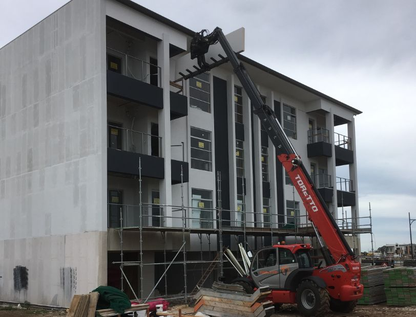 Toretto Transport Telehandler lifting plasterboard sheets up to the third floor of building under construction.