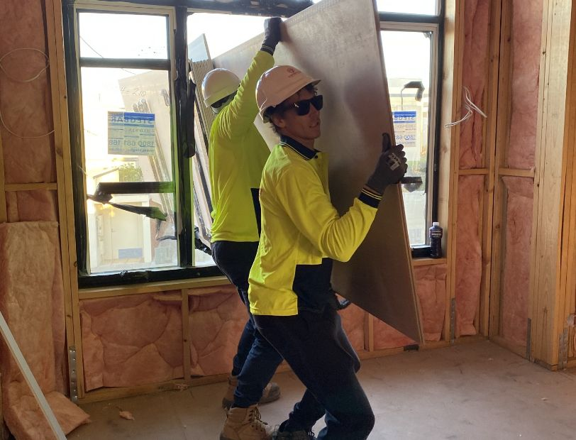 Toretto Transport staff carrying sheet of plasterboard through window.