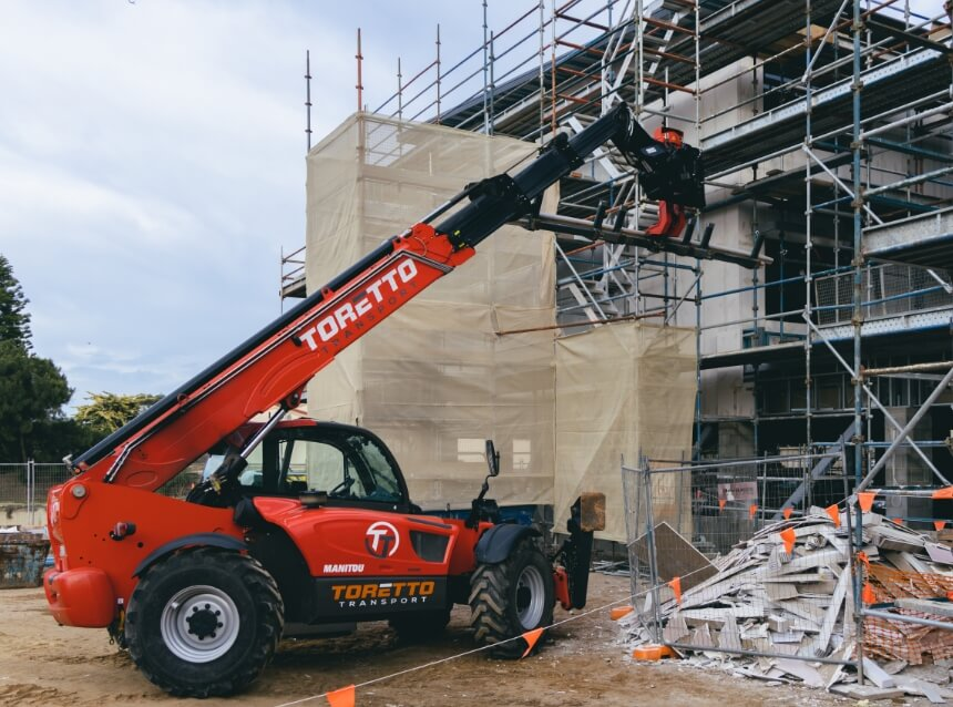 Toretto telehandler with arm extended on job site.