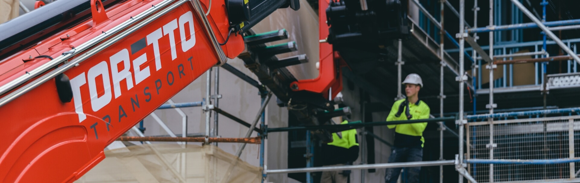 Telehandler lifting plasterboard sheets up to second storey.