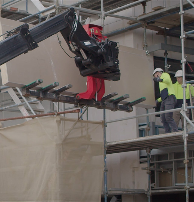 Telehandler lifting plasterboard sheets up to second storey. Toretto staff guiding the sheets safely into position.
