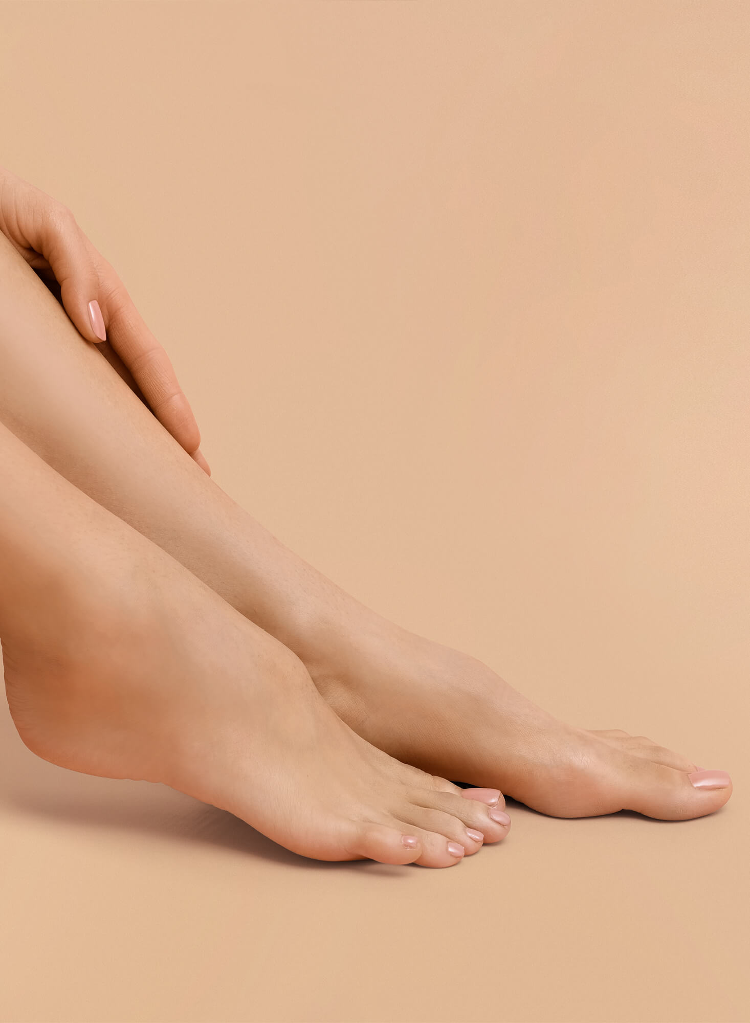 Womans freshly pedicured feet posing one beside the other pointing right with a beige solid background