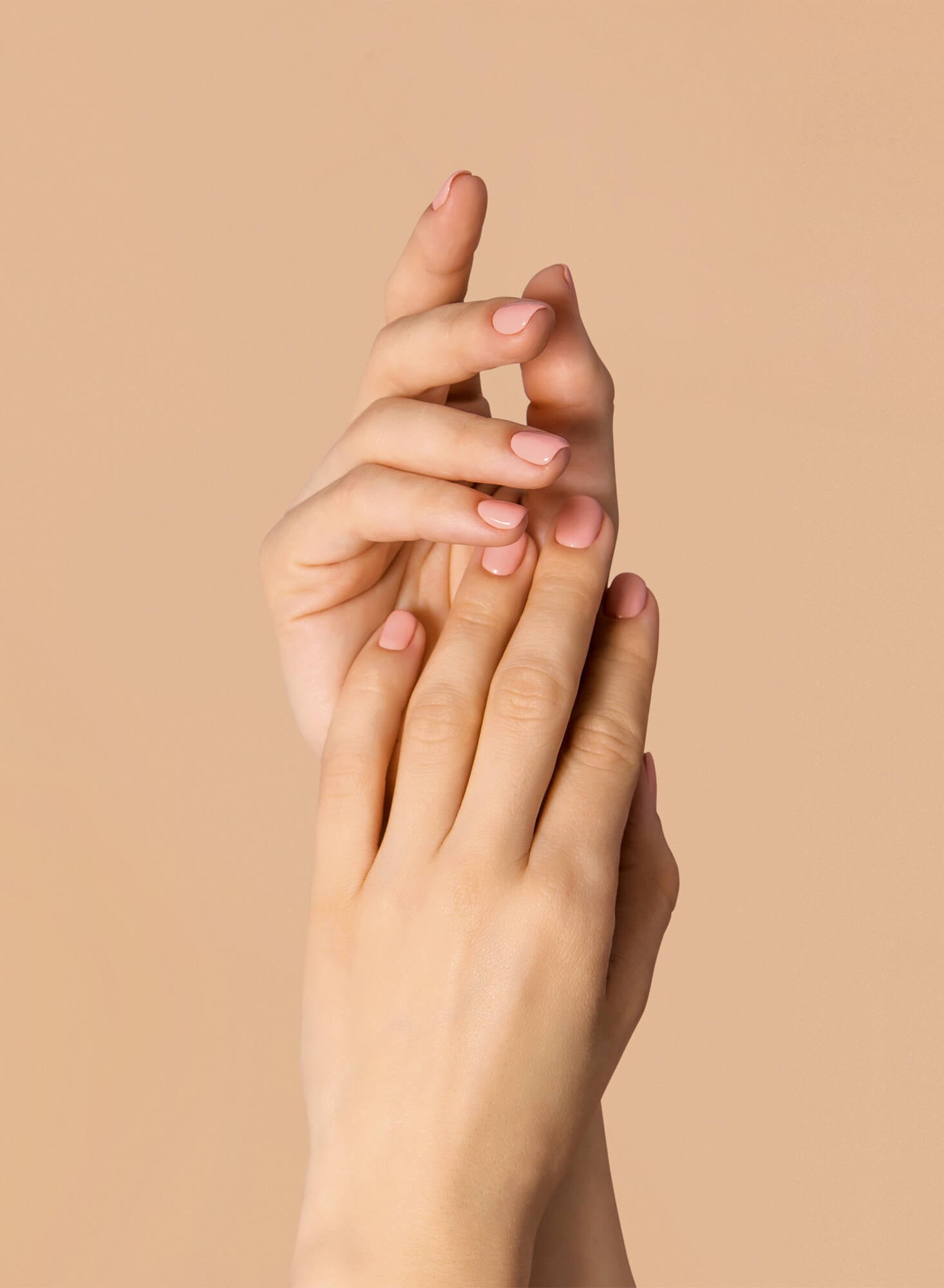 Womans manicured hands, posing one over the other with pink nail polish on a beige background