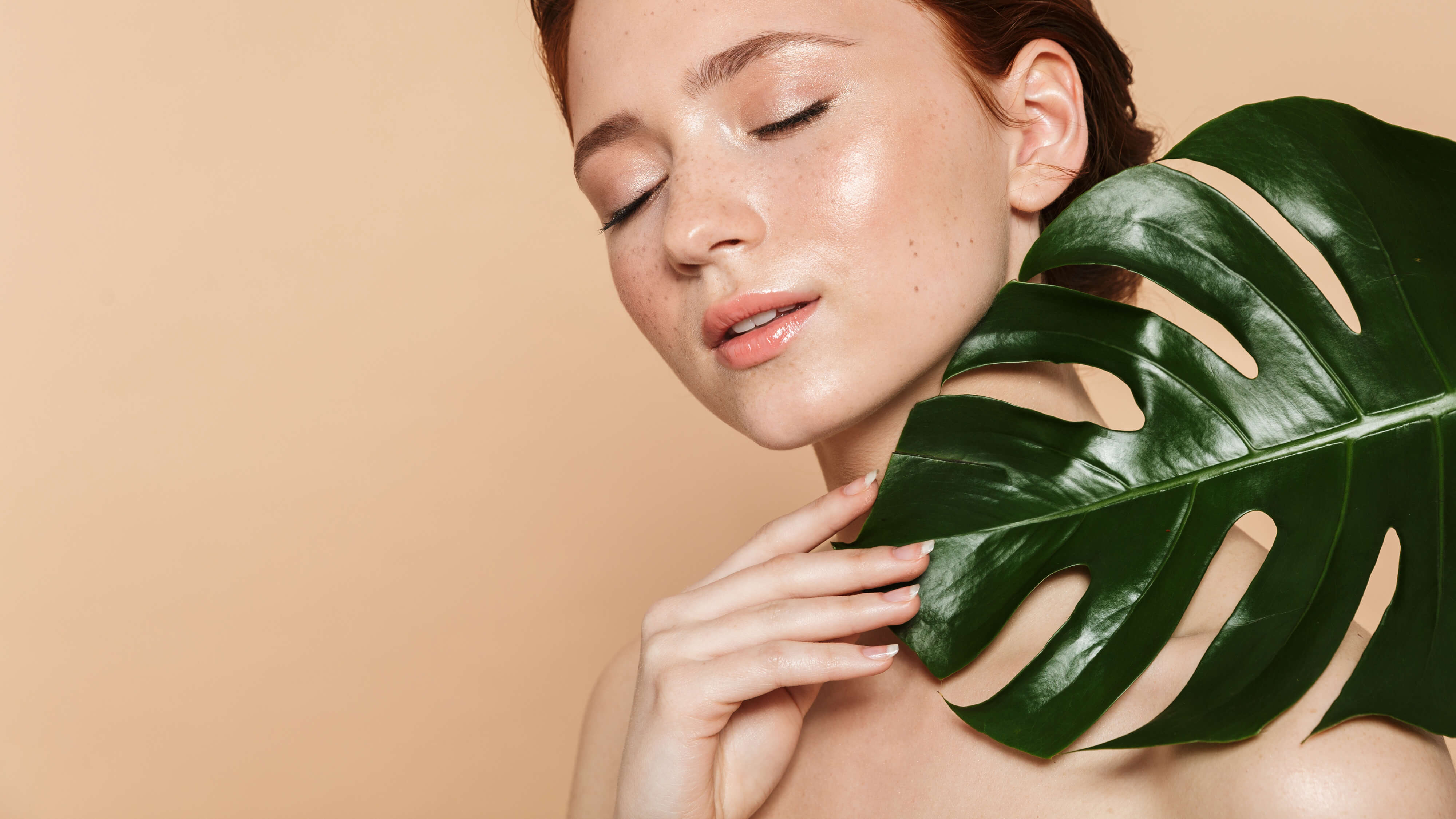 Beautiful red headed woman with eyes closed holding a big green leaf with the tips of her fingers