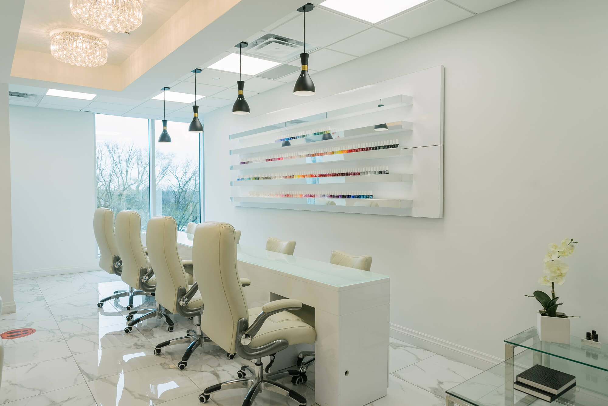 Manicure stations with nail polish selection on white wall at the Nails by Toe Bro Mississauga nail salon