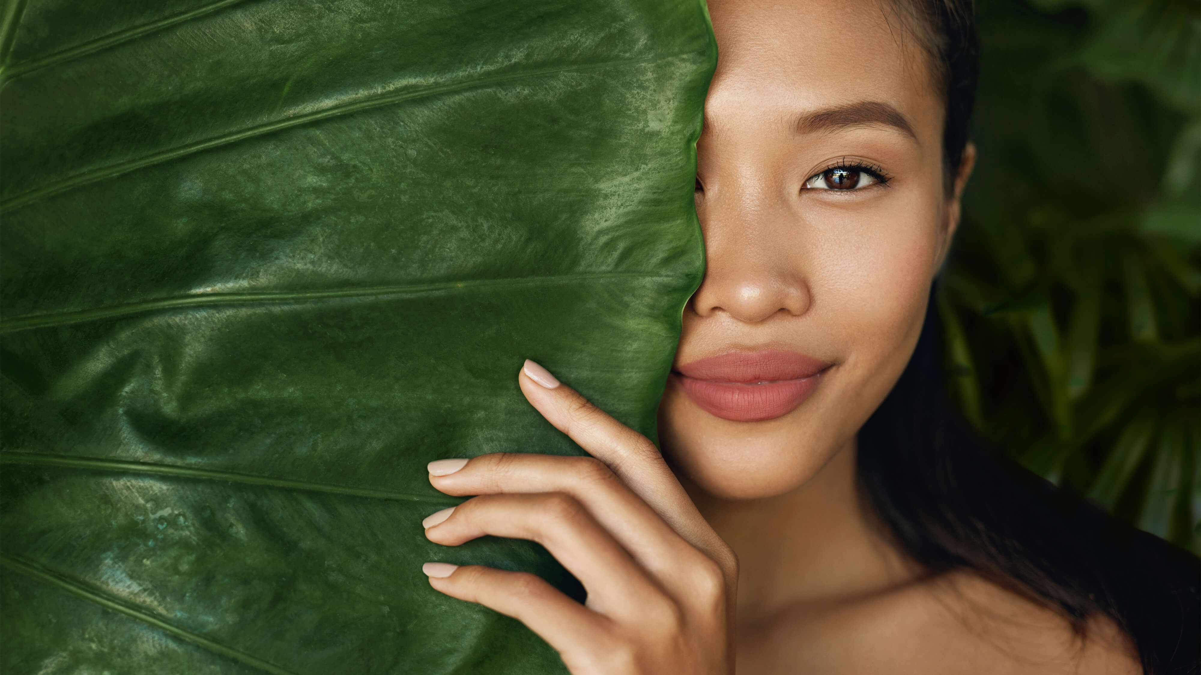 Beautiful model hiding half her face behind a large freen leaf, holding the leaf with one of her manicured hands