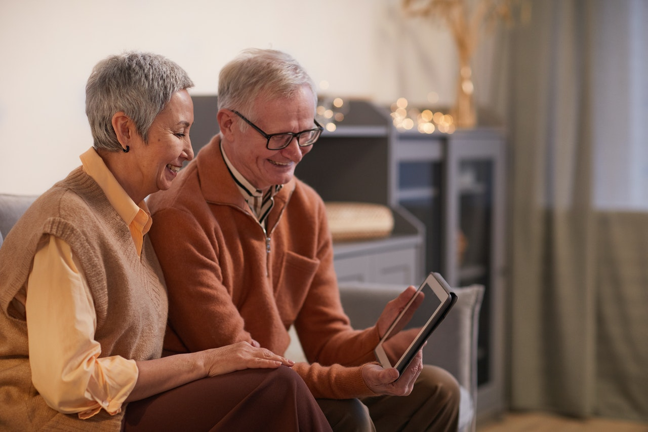 Older couple smiling while looking at ipad Photo by Marcus Aurelius from Pexels