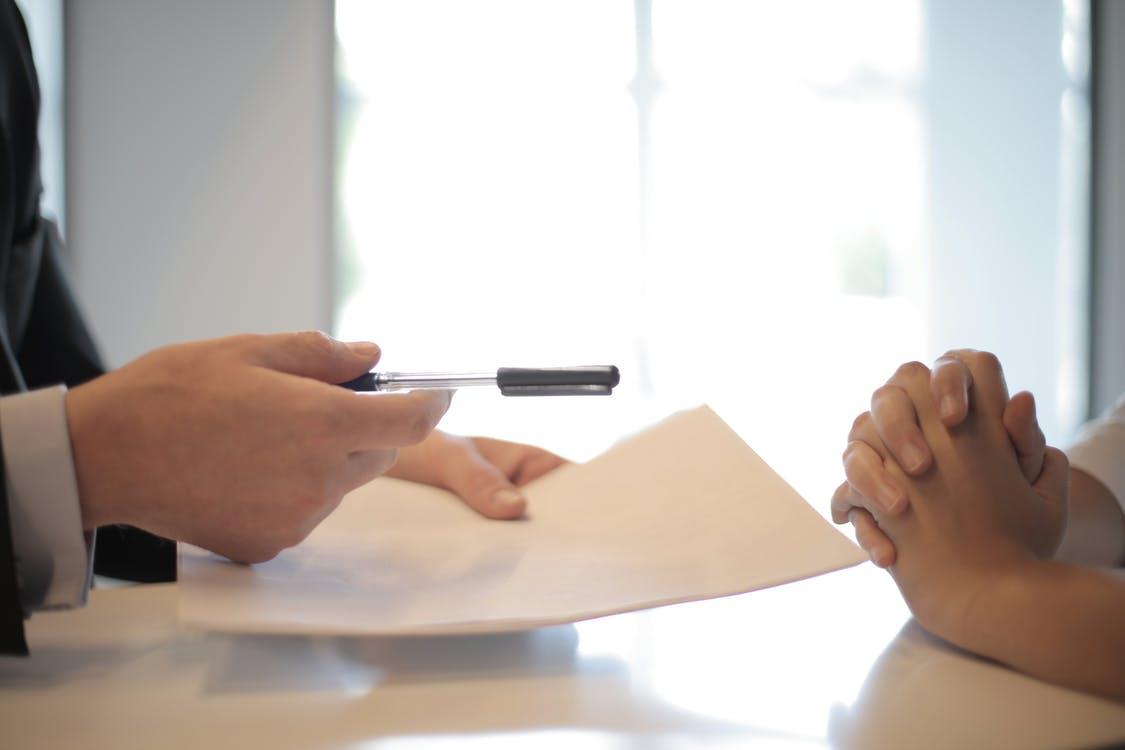Pria memberikan kertas dan pena kepada wanita