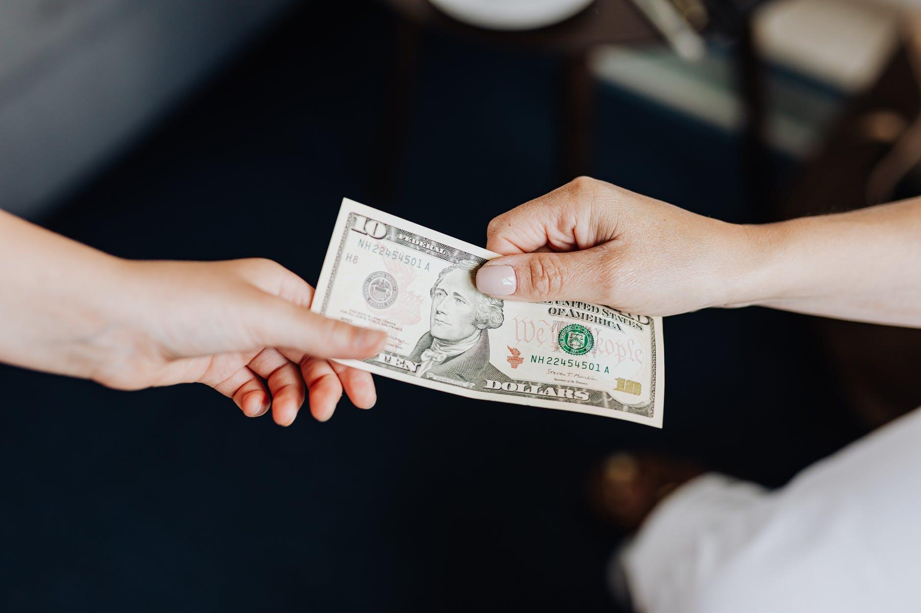 Dua tangan memegang uang kertas dolar