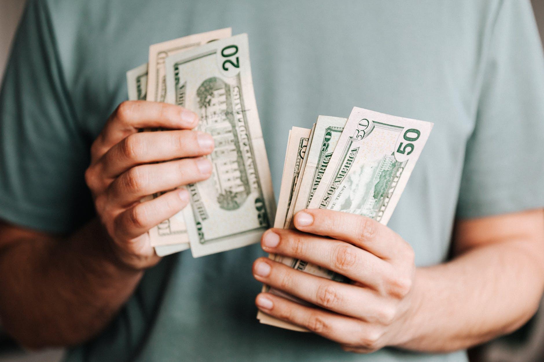 Tangan pria sedang menghitung uang