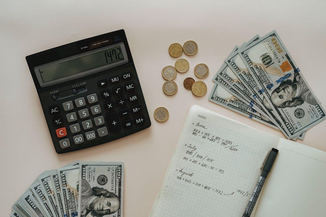 Buku, pena, kalkulator, koin, uang kertas di atas meja
