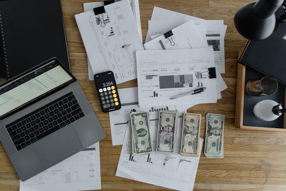 Laptop, ponsel, kertas, pena, uang kertas di atas meja