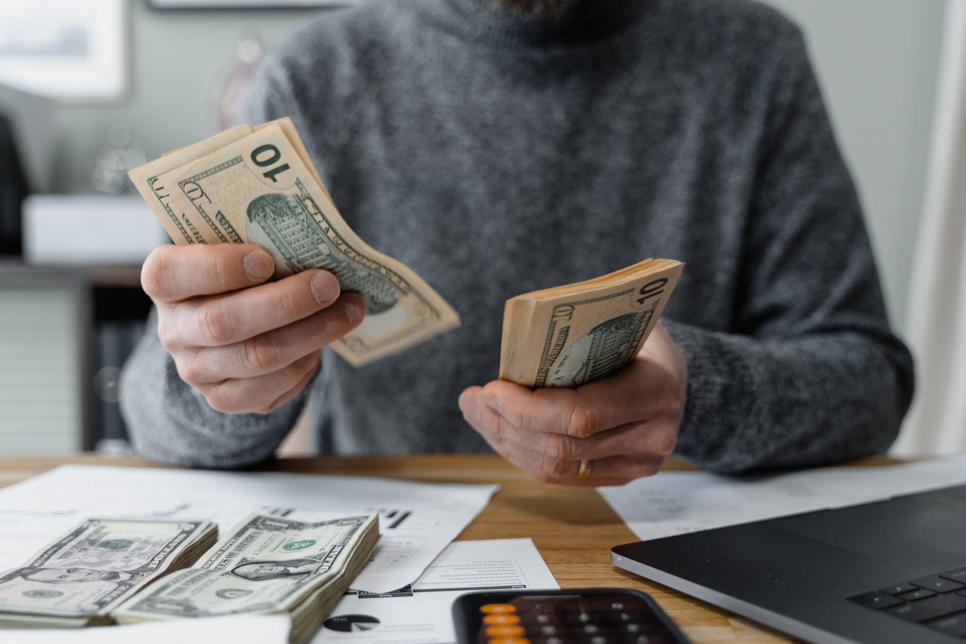 Seorang pria menghitung uang di belakang meja