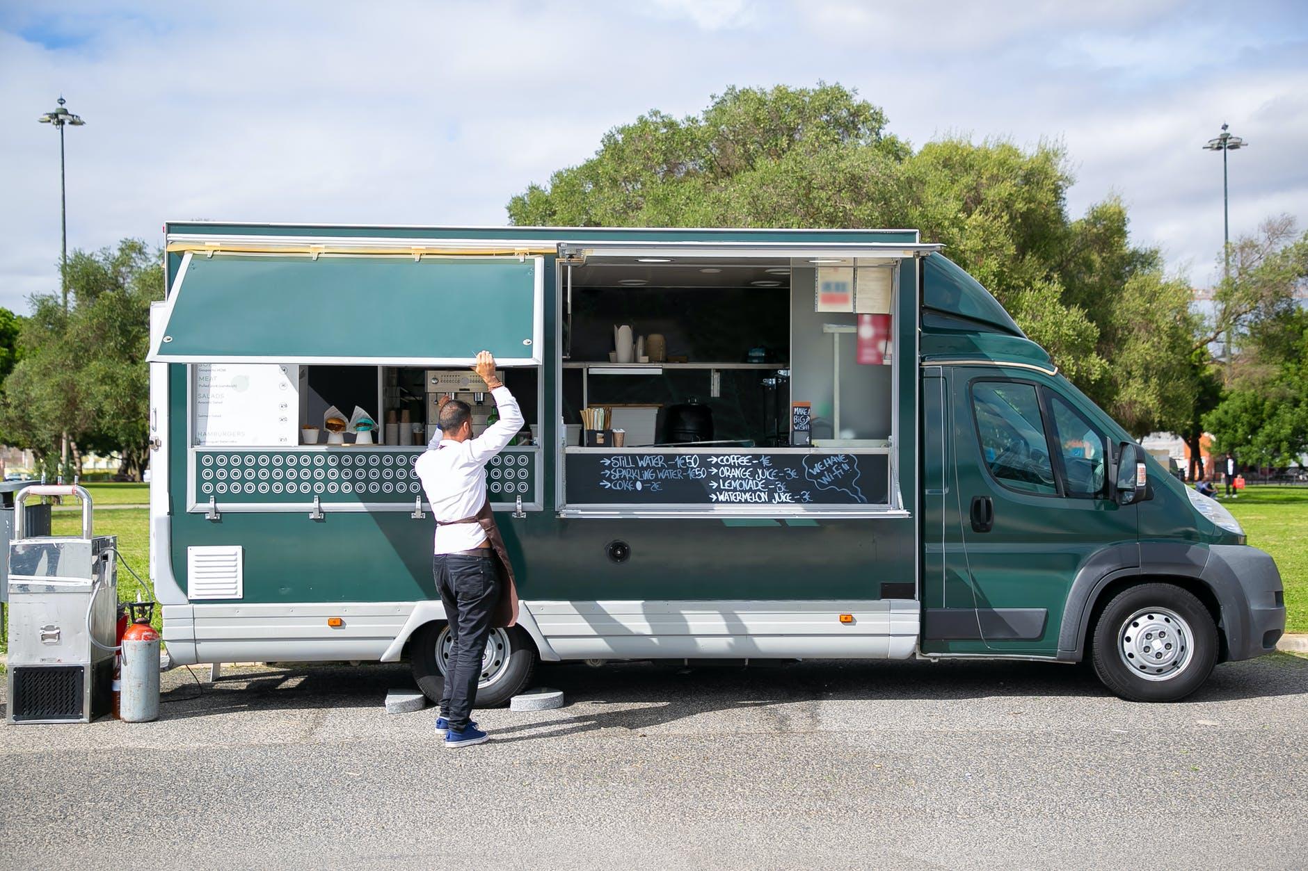 Pria penjual menyiapkan truk makanan untuk bekerja