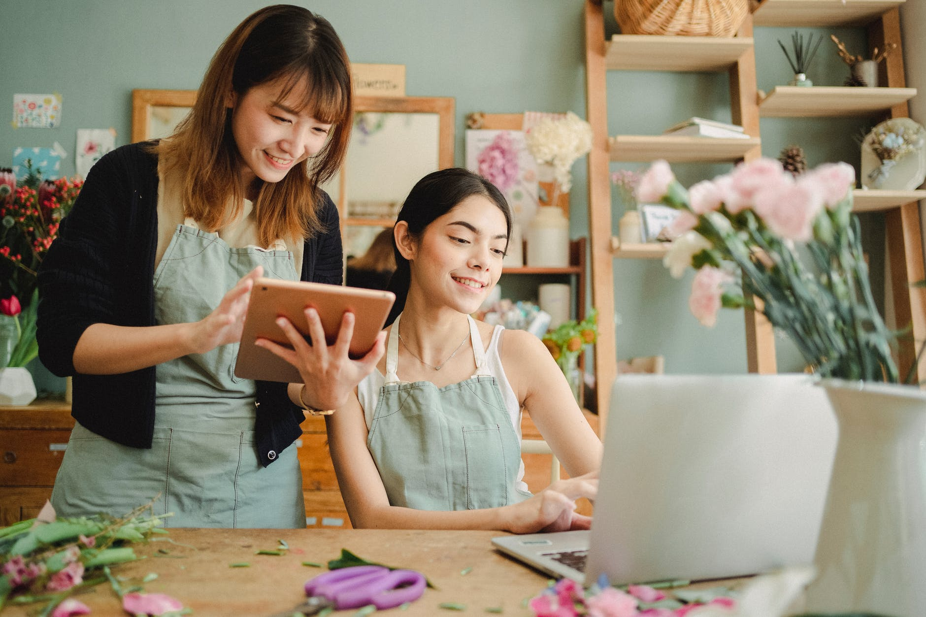 Dua wanita yang bahagia bekerja menggunakan gawai di toko bunga