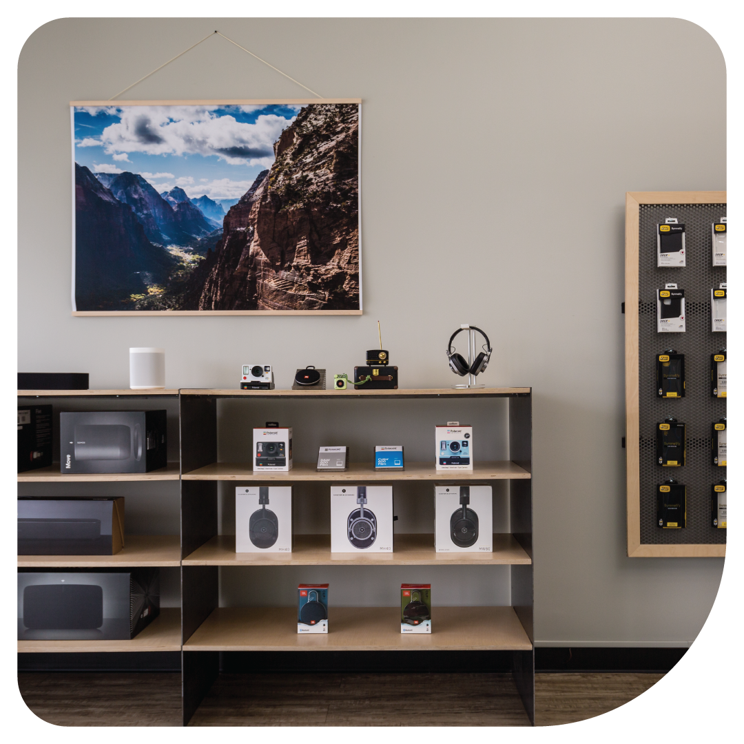 Inside our Fort Collins Apple Repair location. Beats headphones, cameras, and iPhone accessories  in our store with a photo of Fort Collins hanging.
