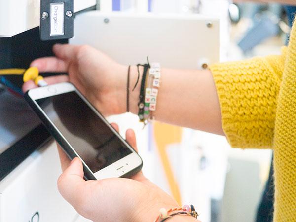 Personne qui branche son téléphone dans une borne de rechargement