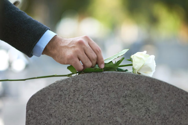 placing a rose on a grave during a funeral