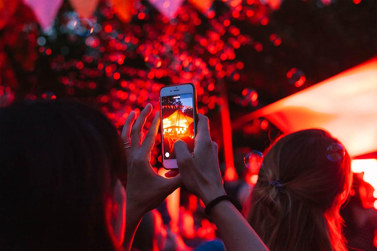 Frau beim Tanzen macht Fotos mit dem Handy von Seifenblasen im dunkeln. Roter Atmosphäre.