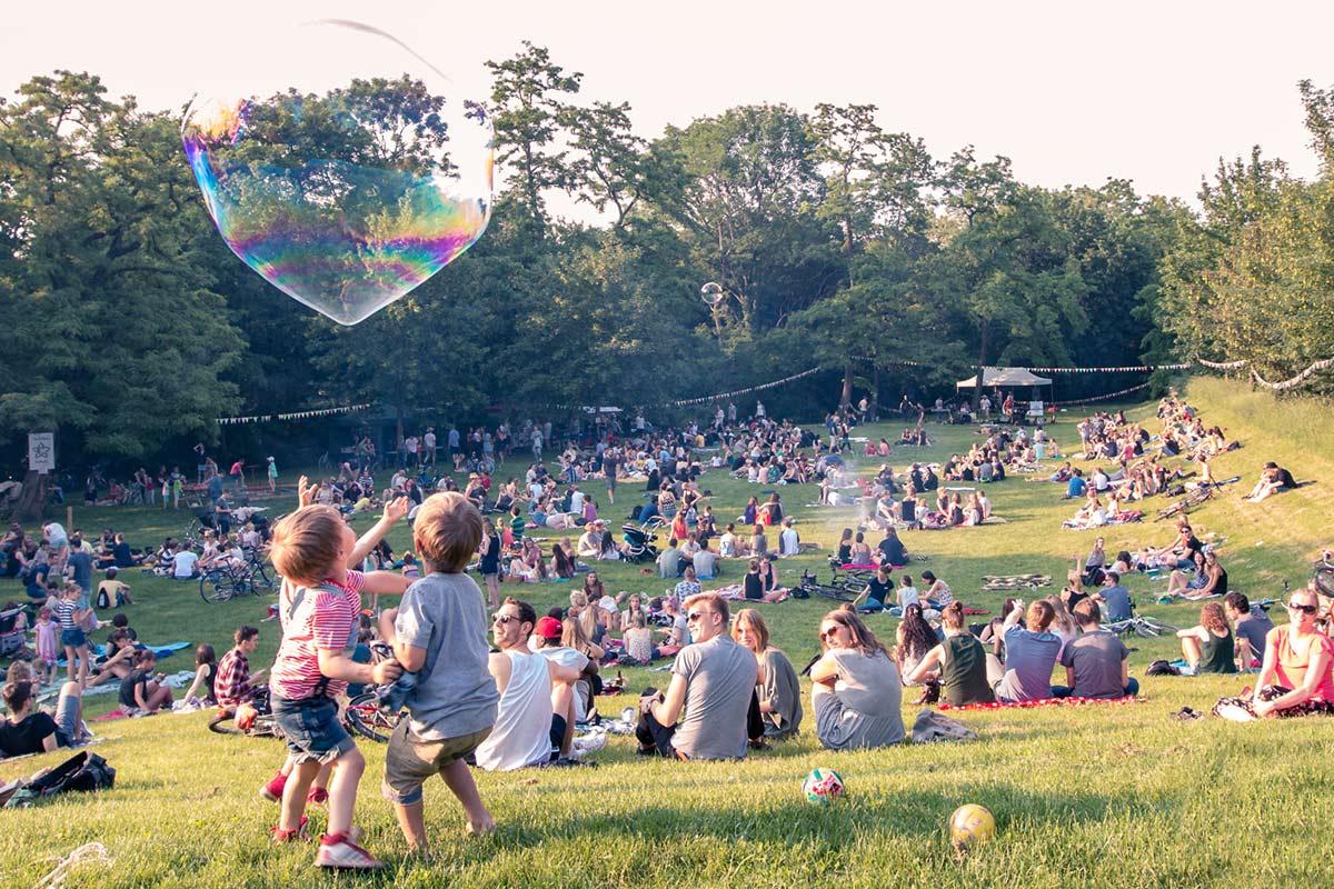 Zwei Kinder spielen mit großen Seifenblasen. Im Hintergrund sind viele Gäste zu sehen.