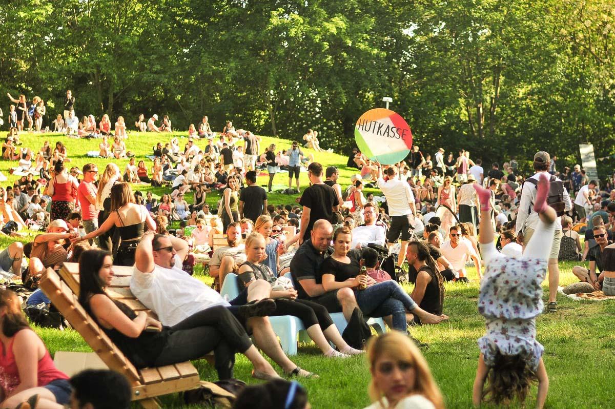 Viele Gäste sind auf der Wiese des GLACIS OPEN AIRS und entspannen in der Sonne.