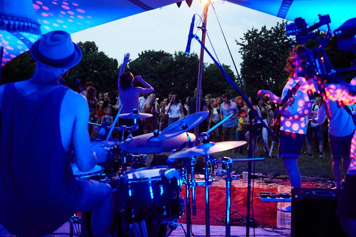 Musiker:innen sind blau beleuchtet unter einem Bühenzelt.