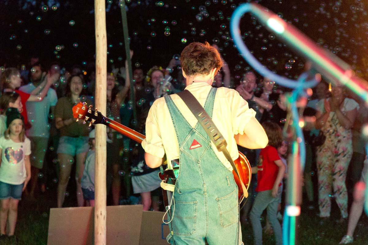 Ein Musiker ist von hinten zu sehen. Er hat Instrumente in der Hand.