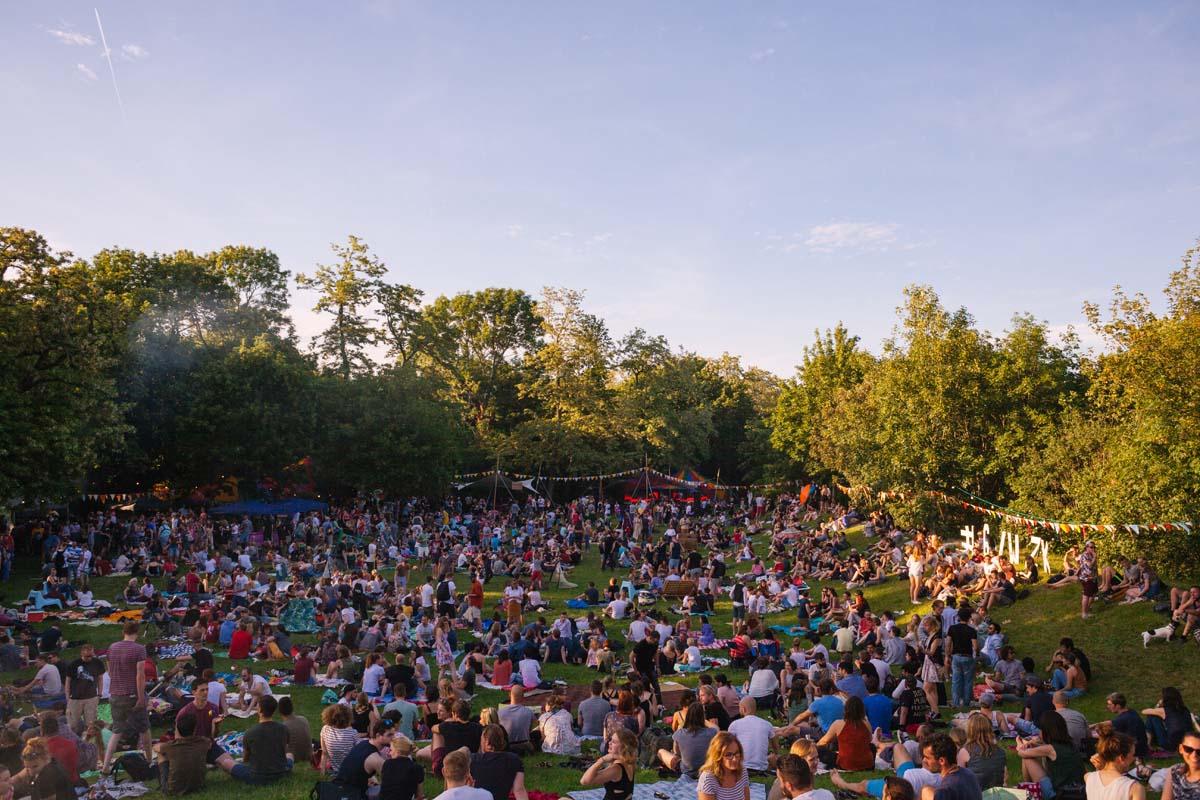 Eine Panoramaaufnahme vom GLACIS OPEN AIR. Viele Gäste sitzen auf der Wiese oder tanzen.