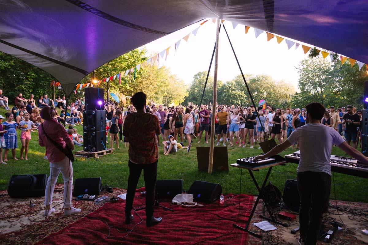 Musiker:innen stehen unter einer Zeltbühne auf Teppichen.
