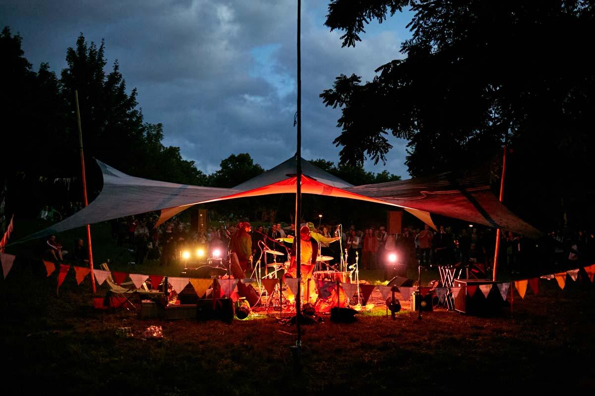 Eine Zeltbühne, unter der eine Band spielt. Es ist bereits am Abend und die Bühne ist beleuchtet.