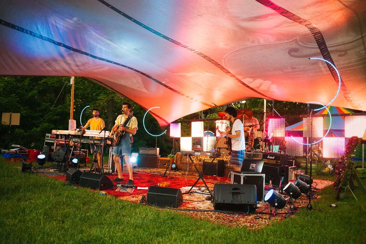 Eine Band steht auf einer Teppichbühne unter einem Zeltdach.