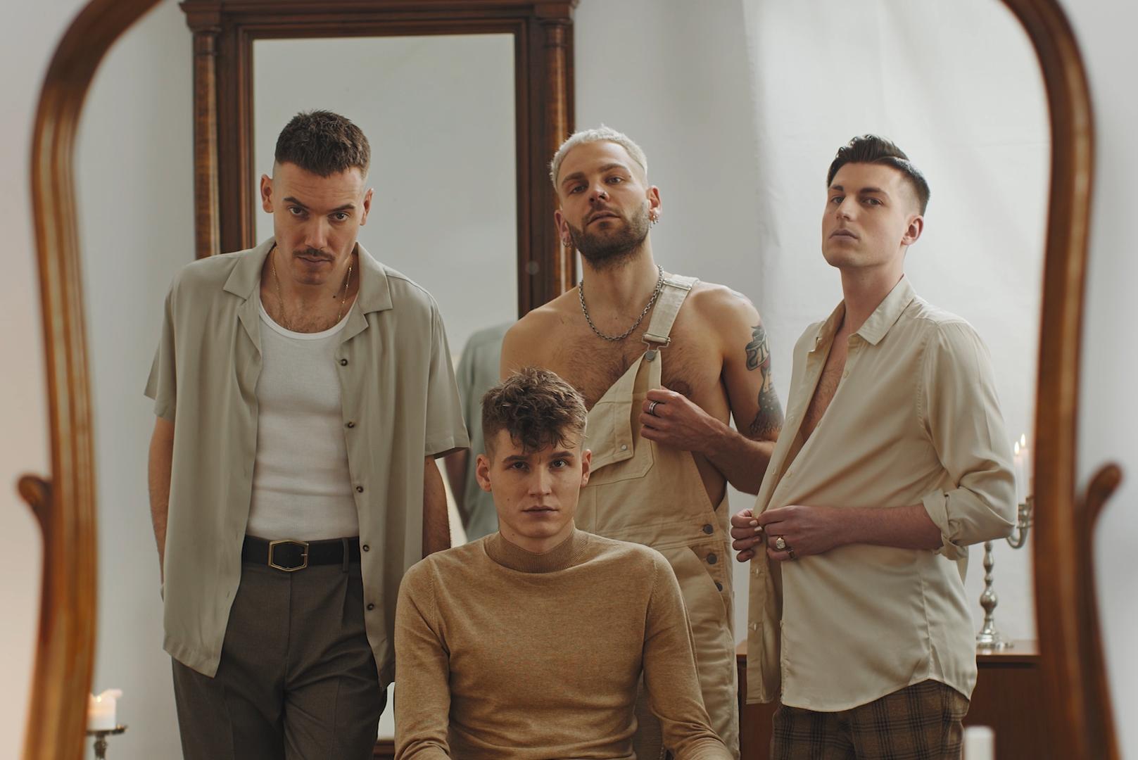 Vier junge Männer stehen zusammen und schauen in die Kamera.