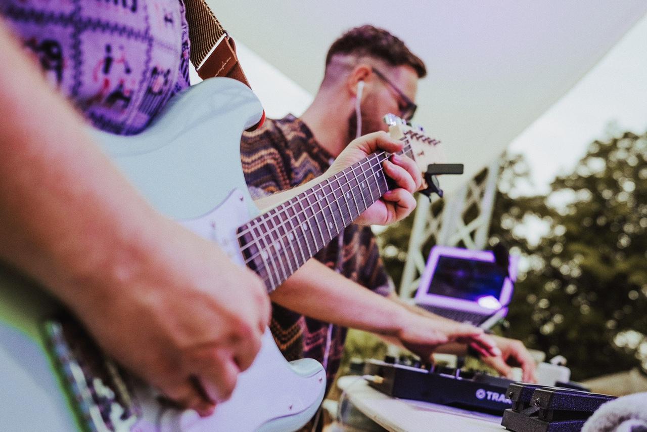 Zwei Männer spielen an Musikinstrumenten.