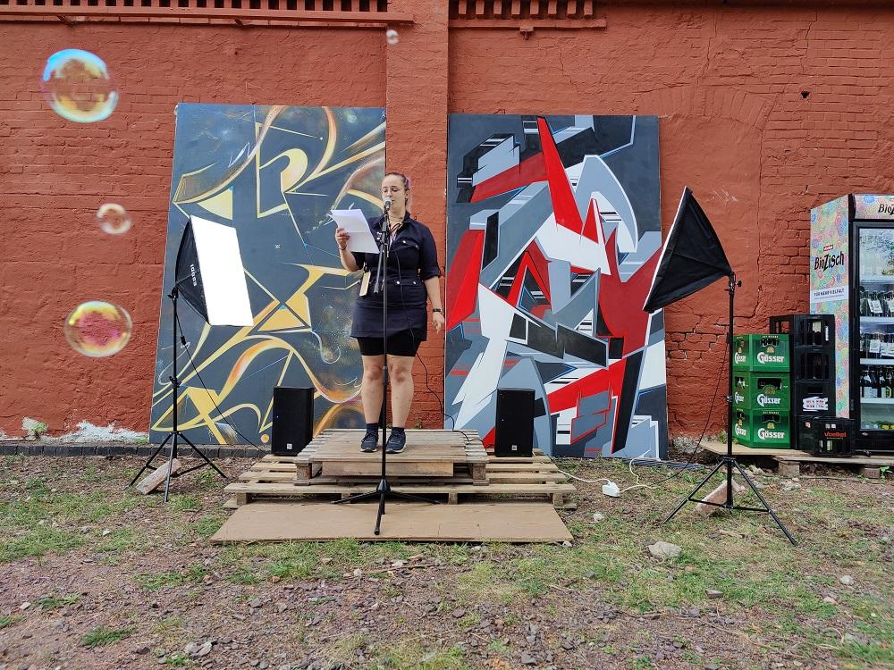 Eine junge blonde Frau steht auf einer kleinen Holzbühne am Mikrofon.