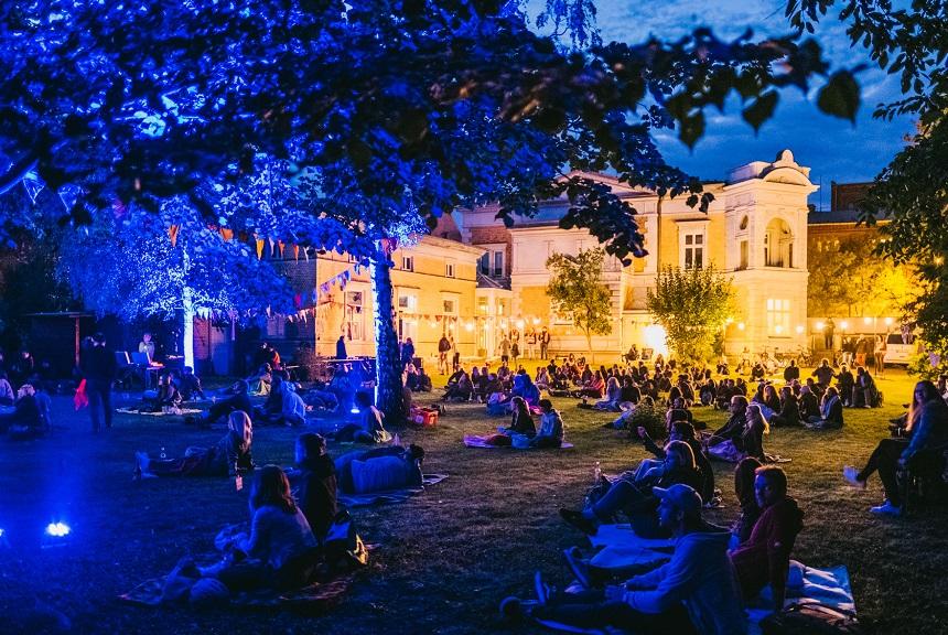 Viele Menschen sitzen in einem großen Garten. Der Garten ist blau beleuchtet.