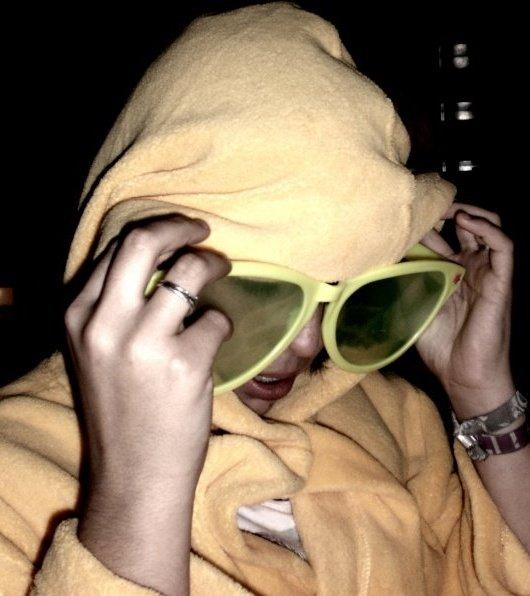 LOMO trägt einen orange farbigen Pullover mit einer Kapuze über den Kopf und einer Sonnenbrille im Gesicht.