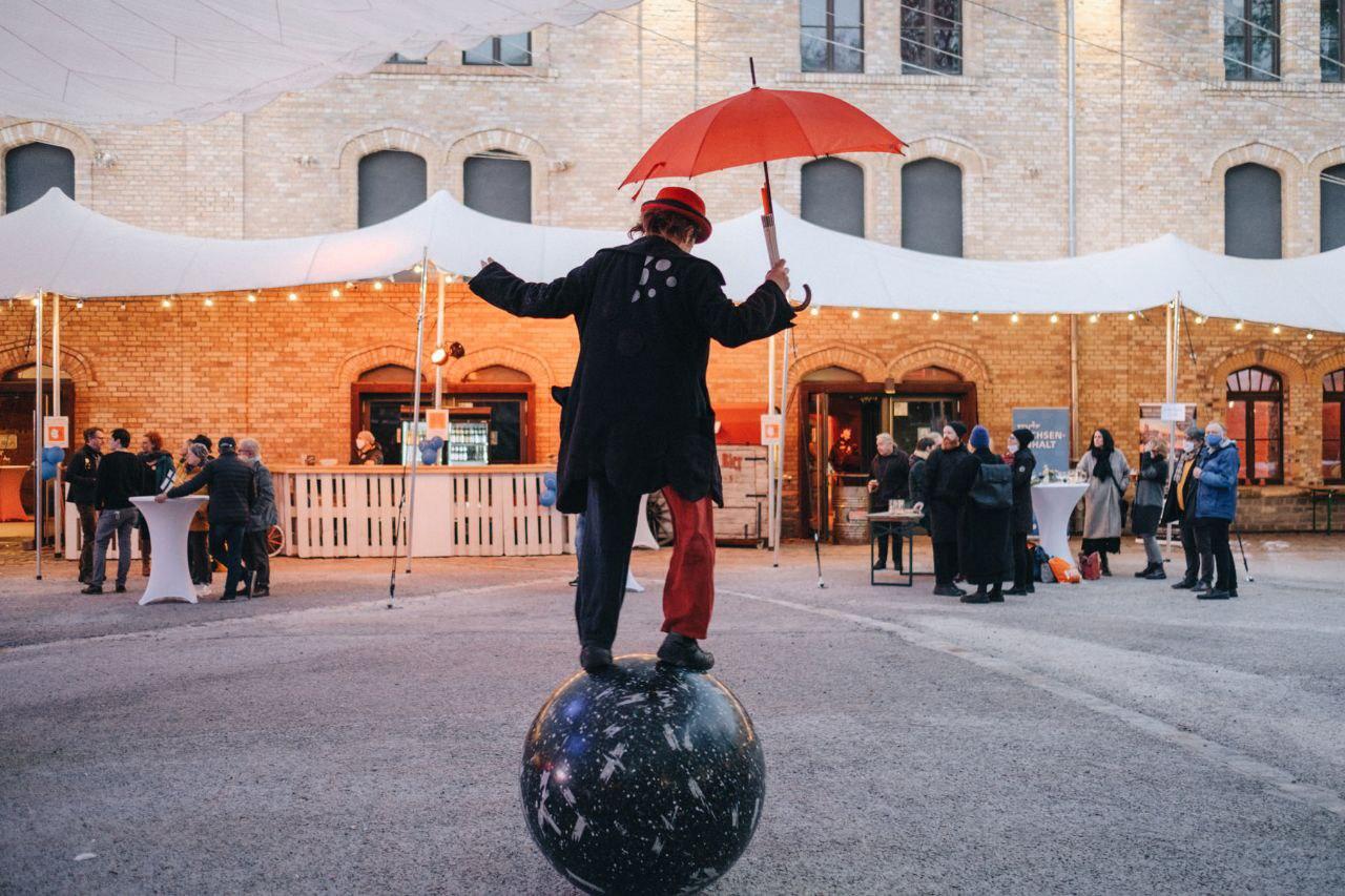 Ein Cirkusclown steht auf einer sich drehenden Kugel.