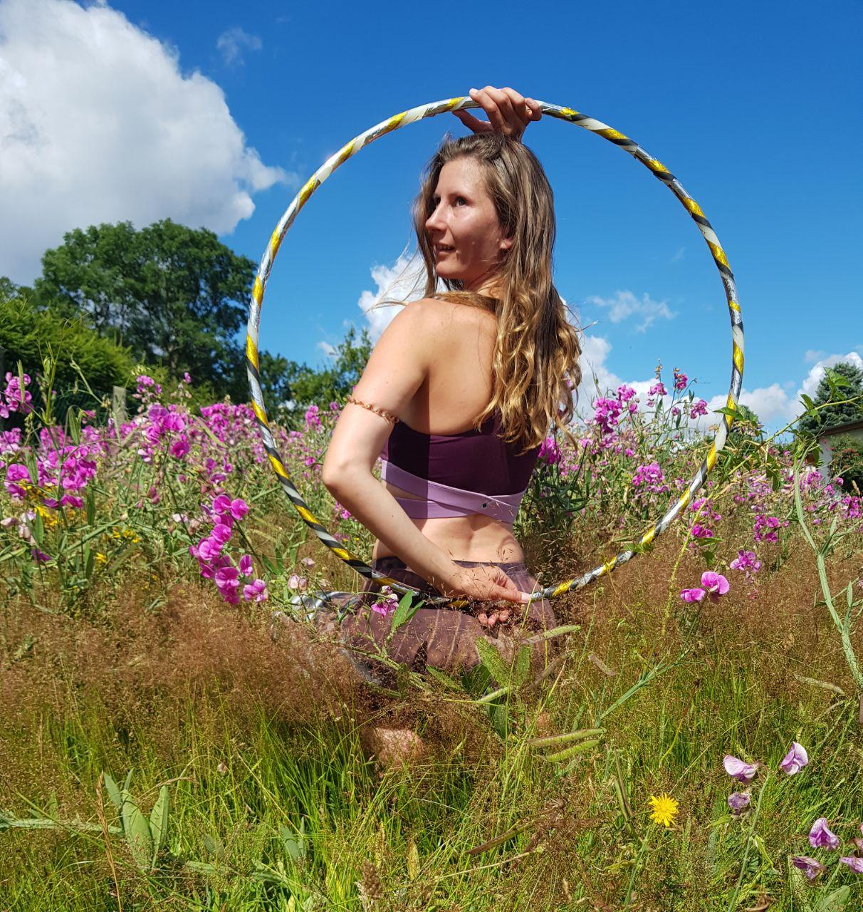 Eine junge blode Frau posiert mit ihrem Hula-Hoop-Reifen.
