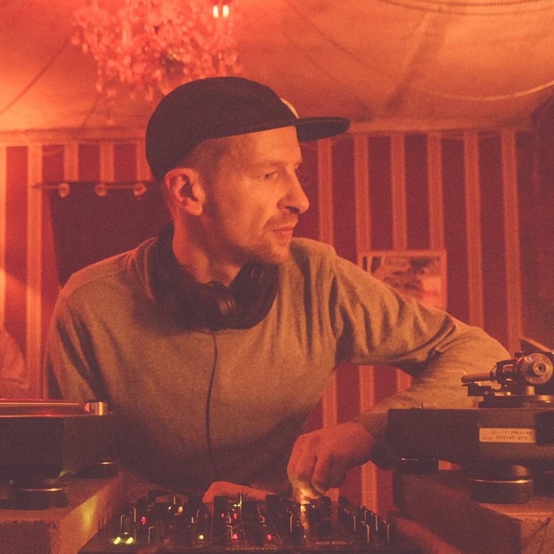 Ein Mann spielt in einem Klub Musik am DJ-Pult.