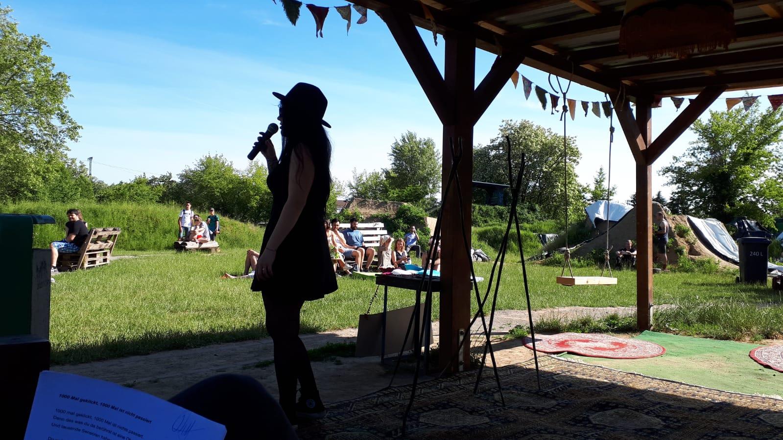 Eine junge Frau trägt einen Hut und steht auf einer Draußenbühne am Mikrofon.