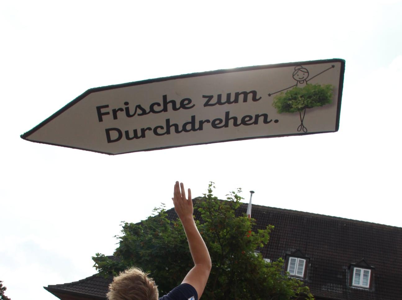 Ein Mann jongliert und tanzt mit einem beschrifteten Schild.