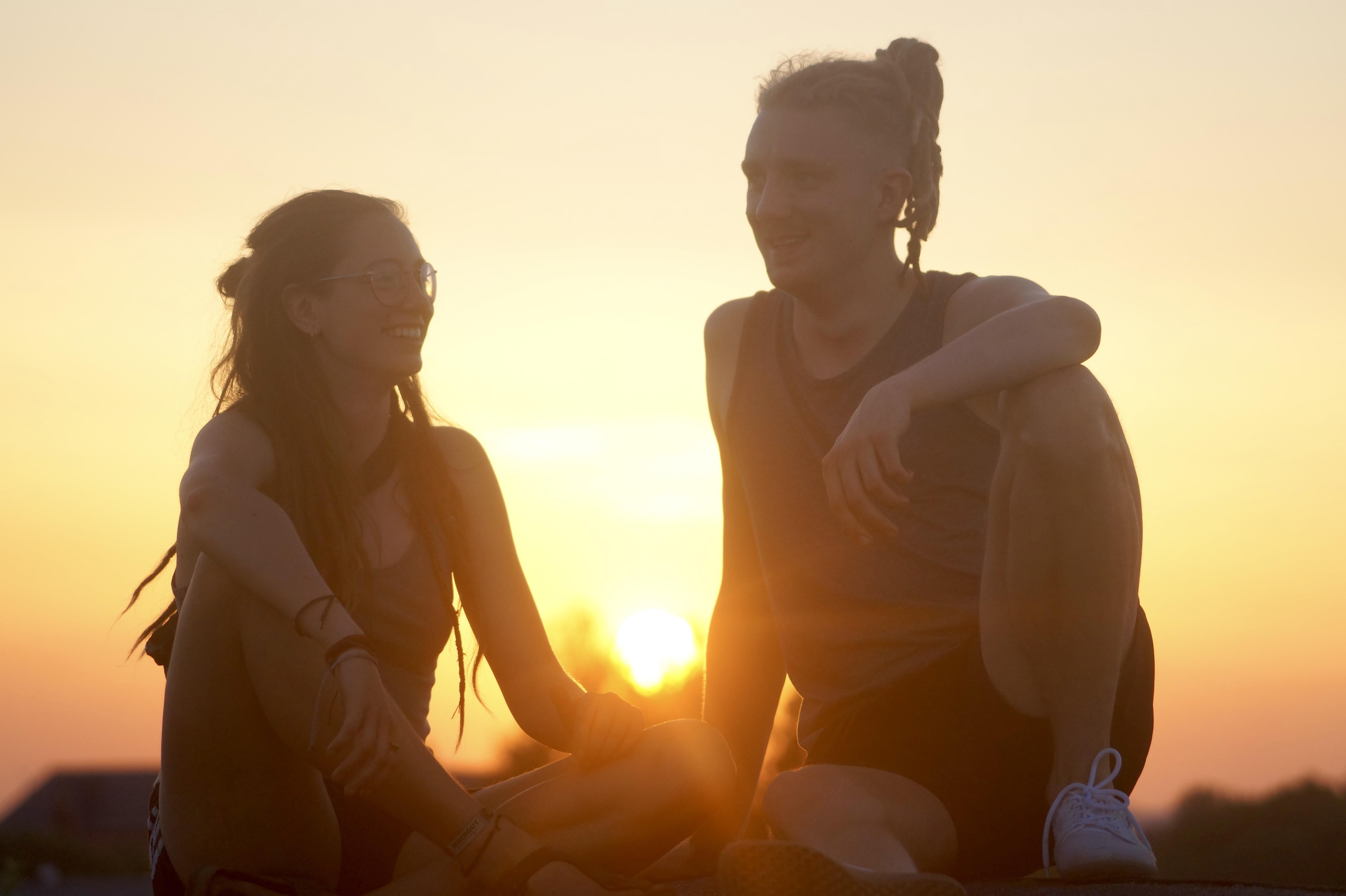 Ein Pärchen hält sich die Hände bei einem Sonnenuntergang.